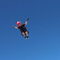 female skydiver in freefall with hot pink helmet