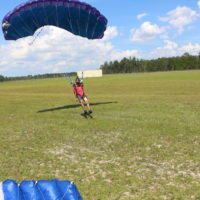 skydiver pulls on toggles as he lands in landing area