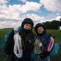 two young women hold their parachutes in landing area