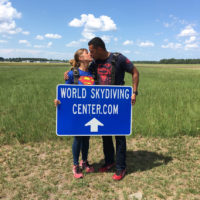 couple kisses holding a sign that says world skydiving center.com