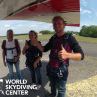 first time tandem skydivers give thumbs up before boarding plane