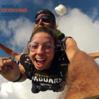 female tandem skydiver smiles in freefall