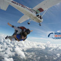 tandem skydiver looks down after exiting plane