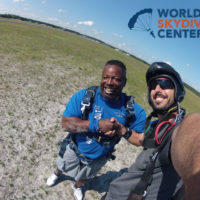 man shakes hands with instructor after landing from skydive