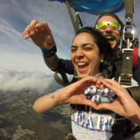 tandem skydiver makes heart with hands under canopy