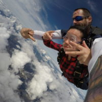tandem skydiver gives peace sign in skydiving freefall