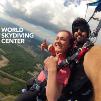 female tandem skydiver smiles and gives thumbs up under canopy