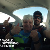 older woman gives thumbs up before exiting plane for skydive