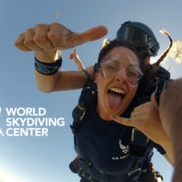 tandem skydiver sticks out her tongue and smiles in freefall