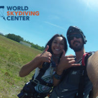 tandem skydiver and instructor give thumbs up after landing